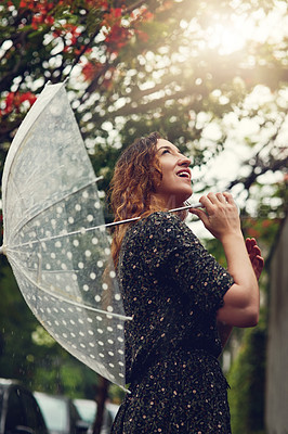 Buy stock photo Cropped shot of a beautiful young woman walking in the rain outside