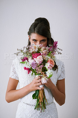 Buy stock photo Studio portrait of a young bride holding a bunch of flowers against a gray background