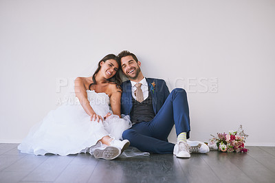 Buy stock photo Studio portrait of a newly married young couple sitting together on the floor against a gray background