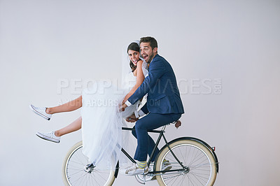Buy stock photo Studio portrait of a newly married young couple riding a bicycle together against a gray background