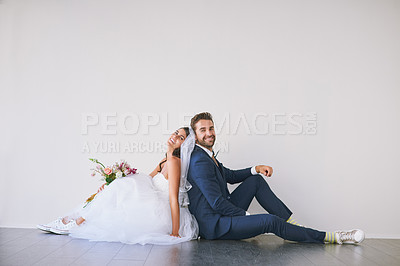 Buy stock photo Studio shot of a newly married young couple sitting back to back on the floor against a gray background