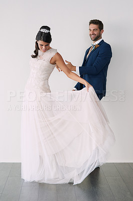 Buy stock photo Studio shot of a newly married young couple standing against a gray background