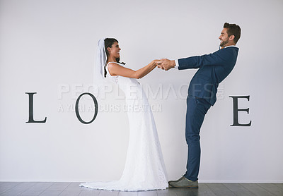 "Buy stock photo Concept studio shot of a bride and groom making an V in the word ""love"" against a wall"