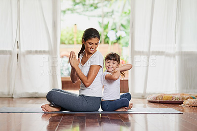 Buy stock photo Shot of a cheerful young mother and daughter doing a yoga pose together while being seated against each other's back