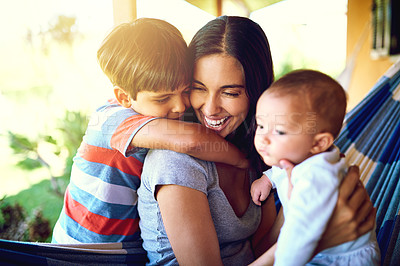 Buy stock photo Shot of a cheerful mother relaxing on a hammock with her two little boys outside at home during the day