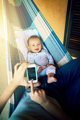 Buy stock photo Shot of an unrecognizable man taking a photo of his baby boy with a cellphone with him lying on a hammock outside at home during the day