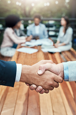 Buy stock photo Closeup shot of two unrecognizable businessmen shaking hands with their colleagues in the background