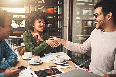 Buy stock photo Shot of two cheerful young work colleagues shaking hands after an successful meeting at a coffeeshop during the day
