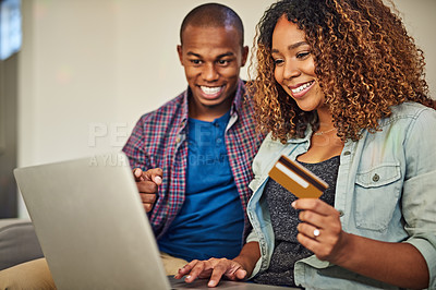 Buy stock photo Shot of a cheerful young couple doing online shopping together while being seated on a couch at home