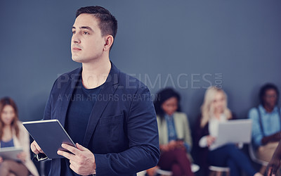 Buy stock photo Cropped shot of a handsome young businessman using a tablet with his colleagues in the background