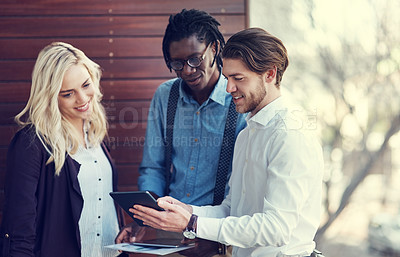 Buy stock photo Cropped shot of three young businesspeople using a tablet while standing outside on the office balcony