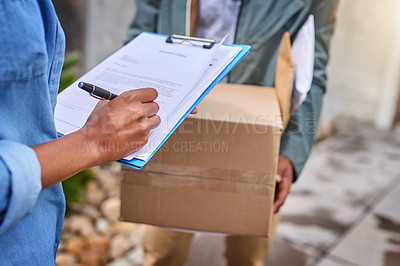 Buy stock photo Closeup shot of an unrecognizable woman signing for her delivery from the courier