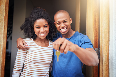 Buy stock photo Portrait of a cheerful young couple standing together in a doorway while holding a pair of keys to their home