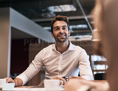 Buy stock photo Shot of a young businessman having a meeting with a colleague in an office