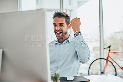 Buy stock photo Shot of a handsome young businessman doing a fist pump while working on a computer in an office