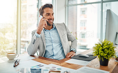 Buy stock photo Shot of a handsome young businessman talking on a cellphone in an office