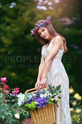 Buy stock photo Shot of a beautiful young woman wearing a floral head wreath and holding a basket full of flowers in nature