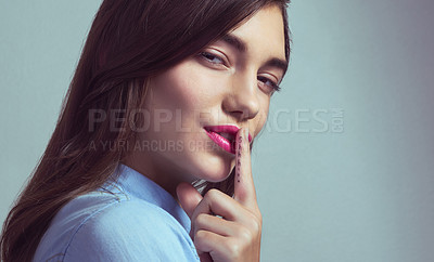 Buy stock photo Studio portrait of an attractive young woman posing with her finger on lips against a grey background