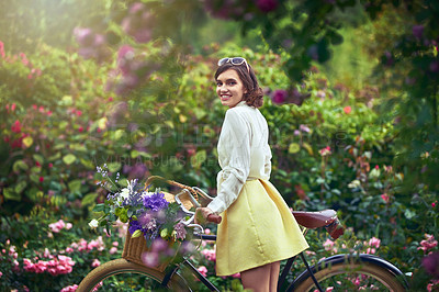 Buy stock photo Portrait of an attractive young woman riding a bicycle outdoors