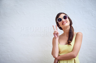 Buy stock photo Studio portrait of a cheerful young woman wearing sunglasses while showing a peace sign against a grey background