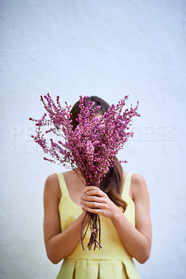 Buy stock photo Studio portrait of an unrecognizable woman holding a bouquet of flowers while standing against a grey background