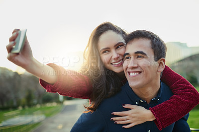 Buy stock photo Shot of a young couple taking selfies while enjoying a piggyback ride outdoors