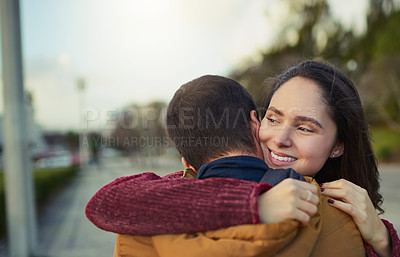 Buy stock photo Shot of a happy young couple embracing each other outdoors