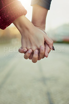 Buy stock photo Cropped shot of a couple holding hands outdoors