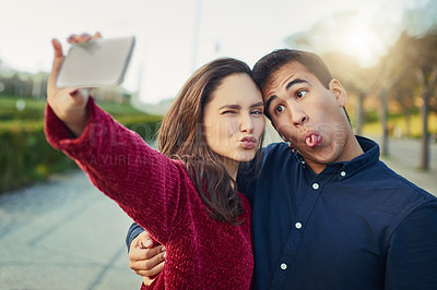 Buy stock photo Shot of a young couple making funny faces while taking a selfie outdoors