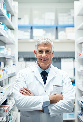 Buy stock photo Cropped portrait of a mature male pharmacist standing with his arms crossed while working in a dispensary