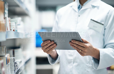 Buy stock photo Cropped shot of an unrecognizable female pharmacist using a tablet while working in a dispensary