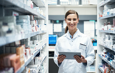Buy stock photo Cropped portrait of a young female pharmacist using a tablet while working in a dispensary