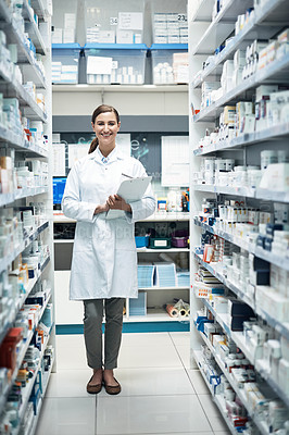 Buy stock photo Full length portrait of a young female pharmacist doing stock take while working in a dispensary