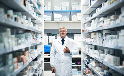 Buy stock photo Cropped portrait of a mature male pharmacist doing stock take while working in a dispensary