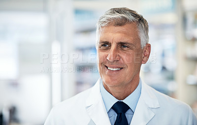 Buy stock photo Shot of a confident mature pharmacist working in a pharmacy