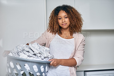 Buy stock photo Shot of a young attractive woman doing laundry at home