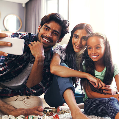 Buy stock photo Cropped shot of a young family taking a selfie at home