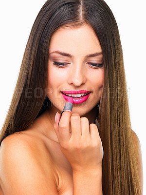 Buy stock photo Studio shot of a beautiful young woman applying pink lipstick against a white background