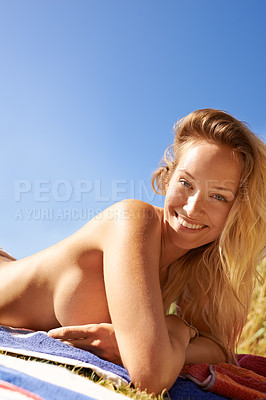 Buy stock photo Cropped shot of an attractive young woman sunbathing on the lawn outside