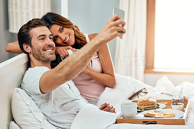Buy stock photo Shot of a happy young couple taking a selfie while enjoying breakfast in bed together at home