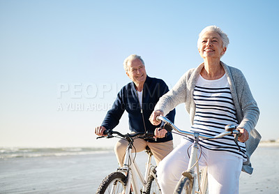 Buy stock photo Shot of a senior married couple riding their bicycles on the beach