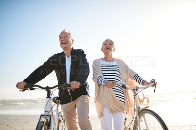 Buy stock photo Shot of a senior married couple with their bicycles on the beach