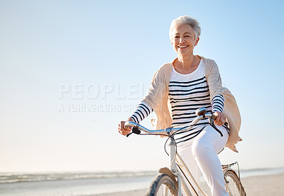 Buy stock photo Shot of a senior woman riding a bicycle on the beach