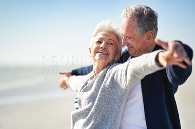 Buy stock photo Shot of a happy senior couple having fun with their arms outstretched at the beach