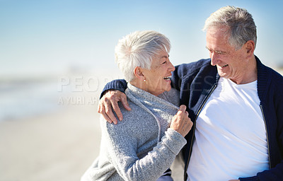 Buy stock photo Shot of a happy senior couple embracing at the beach