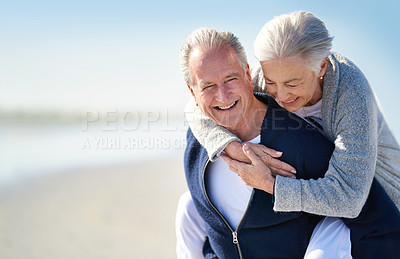 Buy stock photo Shot of a happy senior couple enjoying a piggyback ride at the beach