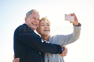 Buy stock photo Shot of a happy senior couple taking selfies outdoors
