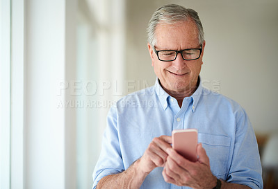 Buy stock photo Shot of a senior man using a mobile phone at home