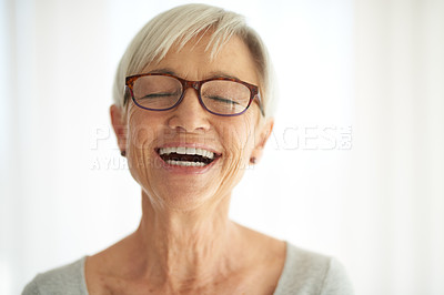 Buy stock photo Shot of a happy senior woman laughing at home