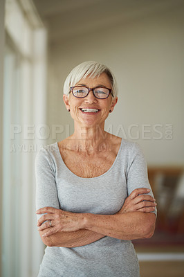 Buy stock photo Shot of a senior woman standing confidently with her arms crossed at home